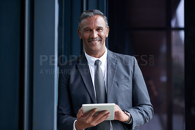 Buy stock photo Portrait of a mature businessman using a digital tablet outside an office