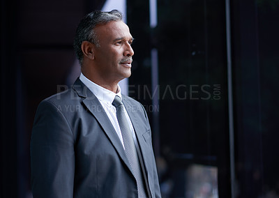 Buy stock photo Shot of a mature businessman looking thoughtful while standing outside an office