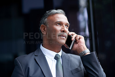 Buy stock photo Shot of a mature businessman talking on a cellphone outside an office