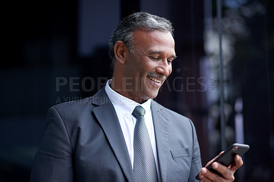 Buy stock photo Shot of a mature businessman using a cellphone while standing outside an office