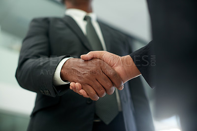 Buy stock photo Closeup shot of two unrecognisable businessmen shaking hands in an office