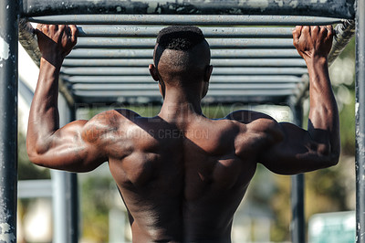 Buy stock photo Shot of a determined young muscular man working out at a calisthenics park outside during the day