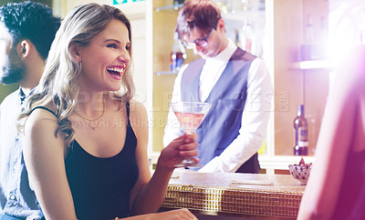 Buy stock photo Shot of two young women toasting with their drinks in a nightclub