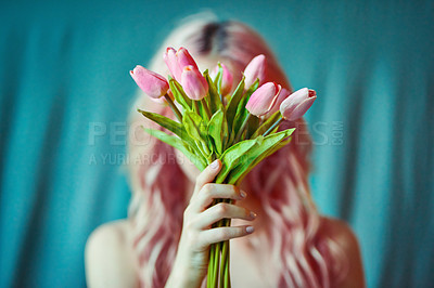 Buy stock photo Cropped shot of a beautiful young woman holding  flowers against a blue background