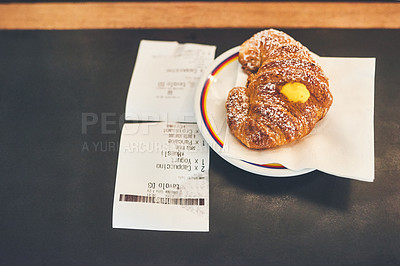 Buy stock photo High angle shot of a pastry treat and the bill right next to each other on a countertop inside of a coffee shop during the day