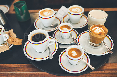 Buy stock photo Shot of a tray of different cups of coffee placed on a countertop inside of a coffee shop during the day