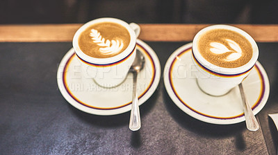 Buy stock photo Shot of two cups of coffee placed next to each other on a countertop inside of a coffee shop during the day