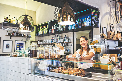 Buy stock photo Portrait of a cheerful young woman standing behind a counter ready to serve a wide selection of backed goods on display inside of a coffee shop