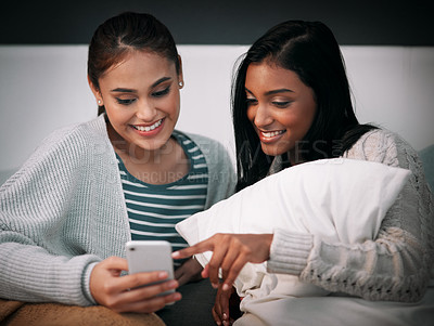 Buy stock photo Shot of a young woman showing her friend something on her cellphone while sitting together on a bed