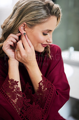 Buy stock photo Cropped shot of a beautiful young bride putting on her earrings while preparing for her wedding in her dressing room
