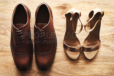 Buy stock photo Still life shot of a bride's and bridegroom's wedding shoes alongside each other on a wooden surface
