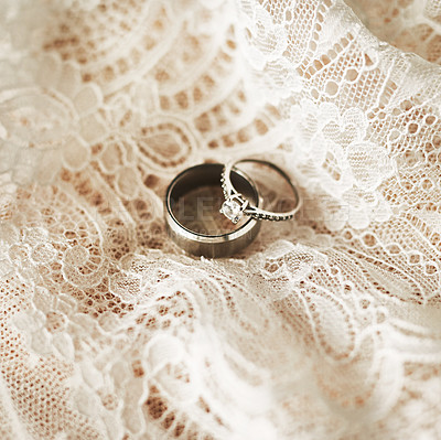 Buy stock photo Still life shot of two beautiful wedding rings on top of a wedding dress