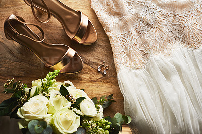 Buy stock photo Still life shot of a bride's shoes, wedding dress and bouquet on a wooden floor