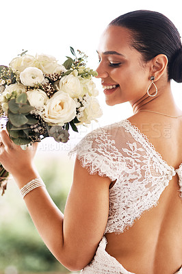 Buy stock photo Shot of a beautiful young bride holding a bouquet of flowers outdoors on her wedding day