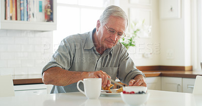 Buy stock photo Shot of a senior man having a leisurely breakfast at home