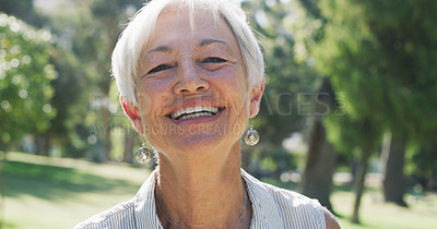 Buy stock photo Cropped portrait of a cheerful senior woman smiling while standing in a park during the day