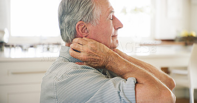 Buy stock photo Shot of a senior man experiencing shoulder pain at home