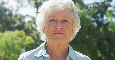 Buy stock photo Cropped shot of a senior woman looking serious while standing in a park during the day