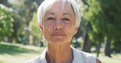 Buy stock photo Closeup portrait of a senior woman looking serious while standing in a park during the day