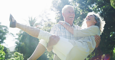 Buy stock photo Cropped shot of an affectionate senior man carrying his wife while enjoying a day at the park