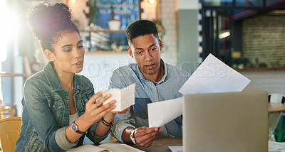 Buy stock photo Cropped shot of two young cafe owners sitting in a coffee shop with a laptop to discuss their financial paperwork