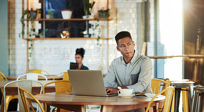 Buy stock photo Cropped shot of a handsome young businessman sitting in a cafe and looking contemplative while using his laptop