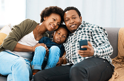 Buy stock photo Shot of a couple sitting with their son while looking at something on a cellphone