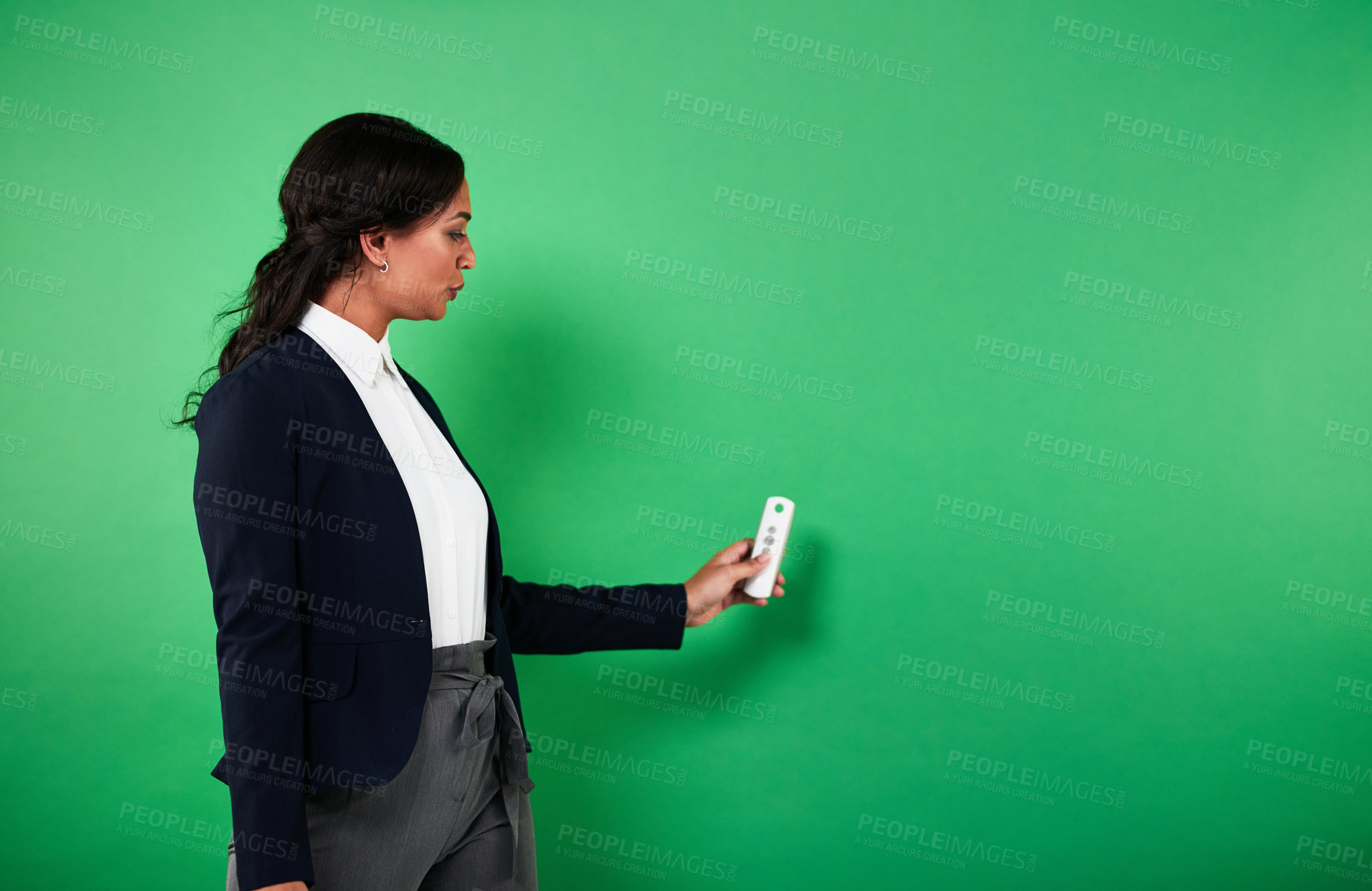 Buy stock photo Cropped shot of an attractive young female weather forecaster reporting the weather  against a green background