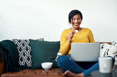 Buy stock photo Cropped shot of an attractive young woman sitting on her sofa and eating potato crisps while using her laptop