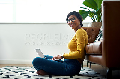 Buy stock photo Cropped shot of an attractive young woman sitting crosslegged on the floor and using her laptop at home