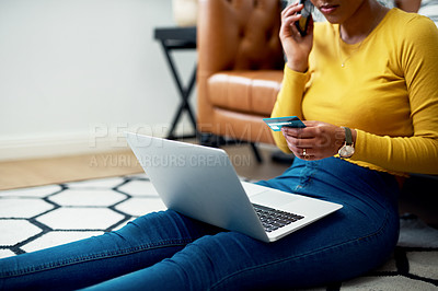 Buy stock photo Cropped shot of an unrecognizable woman sitting on her floor at home and using technology for online shopping