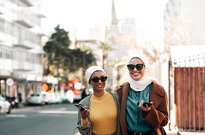 Buy stock photo Cropped shot of two attractive young muslim women wearing sunglasses and holding their cellphones while city sight-seeing