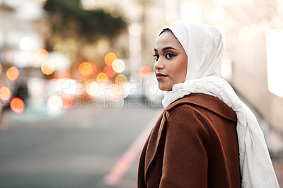 Buy stock photo Cropped shot of an attractive young woman wearing a hijab and standing alone while touring the city