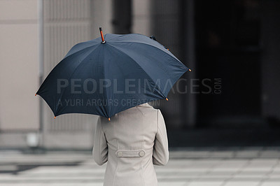 Buy stock photo Rearview shot of an unrecognizable businesswoman holding an umbrella while standing outside in the rain