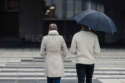 Buy stock photo Rearview shot of an unrecognizable couple walking together while holding an umbrella outside in the rain