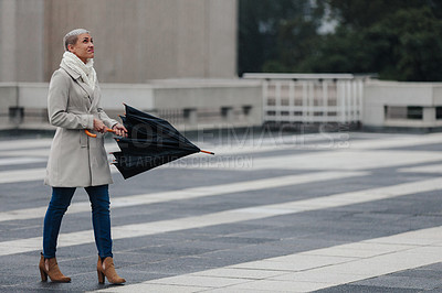 Buy stock photo Cropped shot of an attractive young businesswoman holding an umbrella while walking outside in the rain