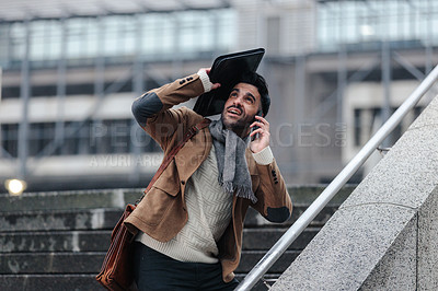 Buy stock photo Cropped shot of a handsome young businessman talking on his cellphone outside  while trying to protect himself from the rain using a bag