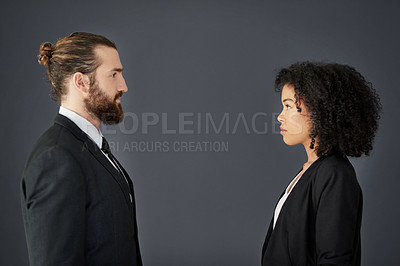Buy stock photo Studio shot of two young corporate businesspeople posing facing each other against a grey background