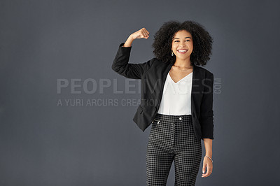 Buy stock photo Studio portrait of an attractive young corporate businesswoman flexing her bicep against a grey background