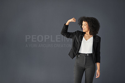 Buy stock photo Studio shot of an attractive young corporate businesswoman flexing her bicep against a grey background