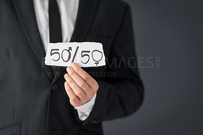 Buy stock photo Studio shot of an unrecognizable businessman holding a piece of paper promoting gender equality against a grey background