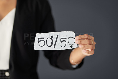 Buy stock photo Studio shot of an unrecognizable businesswoman holding a piece of paper promoting gender equality against a grey background