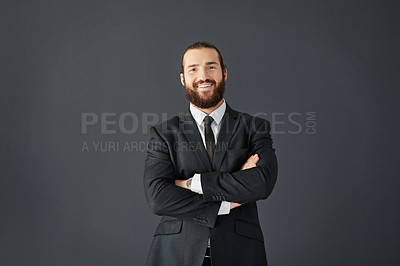 Buy stock photo Studio portrait of a handsome young corporate businessman posing with his arms folded against a grey background
