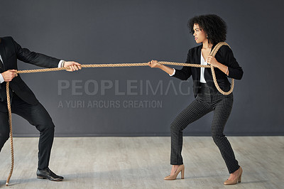 Buy stock photo Full length shot of two corporate businesspeople pulling a rope during a tug of war against a grey background