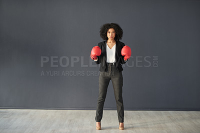 Buy stock photo Full length shot of a young corporate businesswoman posing wearing boxing gloves against a grey background