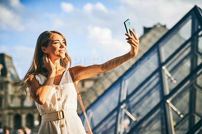 Buy stock photo Shot of a beautiful young woman taking selfies while exploring the city of Paris