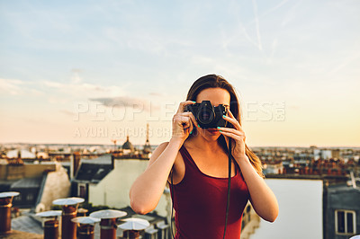 Buy stock photo Shot of an attractive young woman standing on a rooftop and taking pictures of the beautiful city of Paris, France