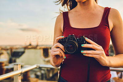 Buy stock photo Cropped shot of an unrecognizable woman standing on a rooftop and taking pictures of the beautiful city of Paris, France