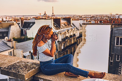 Buy stock photo Shot of an attractive young woman sitting on a rooftop and taking pictures of the beautiful city of Paris, France