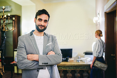 Buy stock photo Cropped portrait of a handsome young male receptionist standing with his arms crossed in a hotel